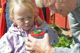 Eldre dame og barn ser på innholdet i en lupeboks
